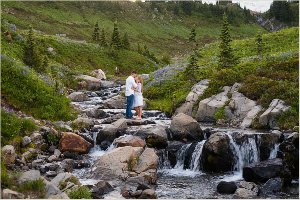Adventurous Couple Standing in Waterfall at Mount Rainier Washington Engagement Session