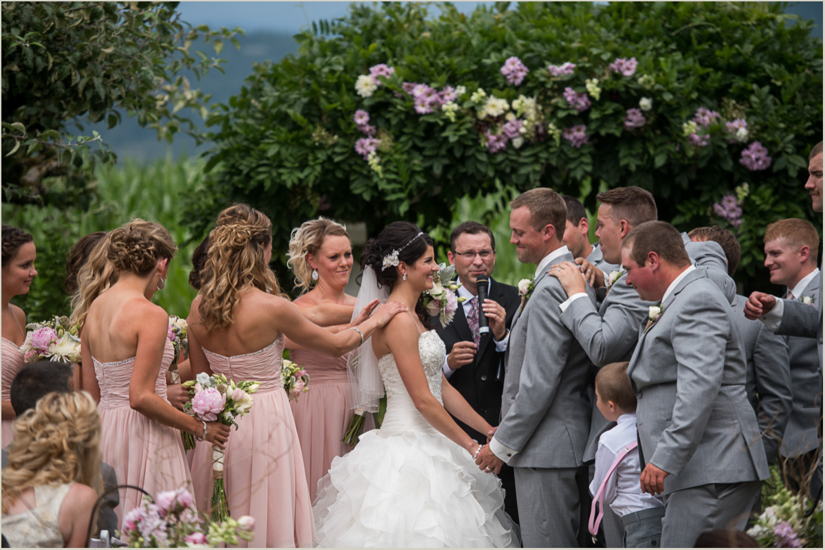 Bridal Party Prays over Bride and Groom During Ceremony