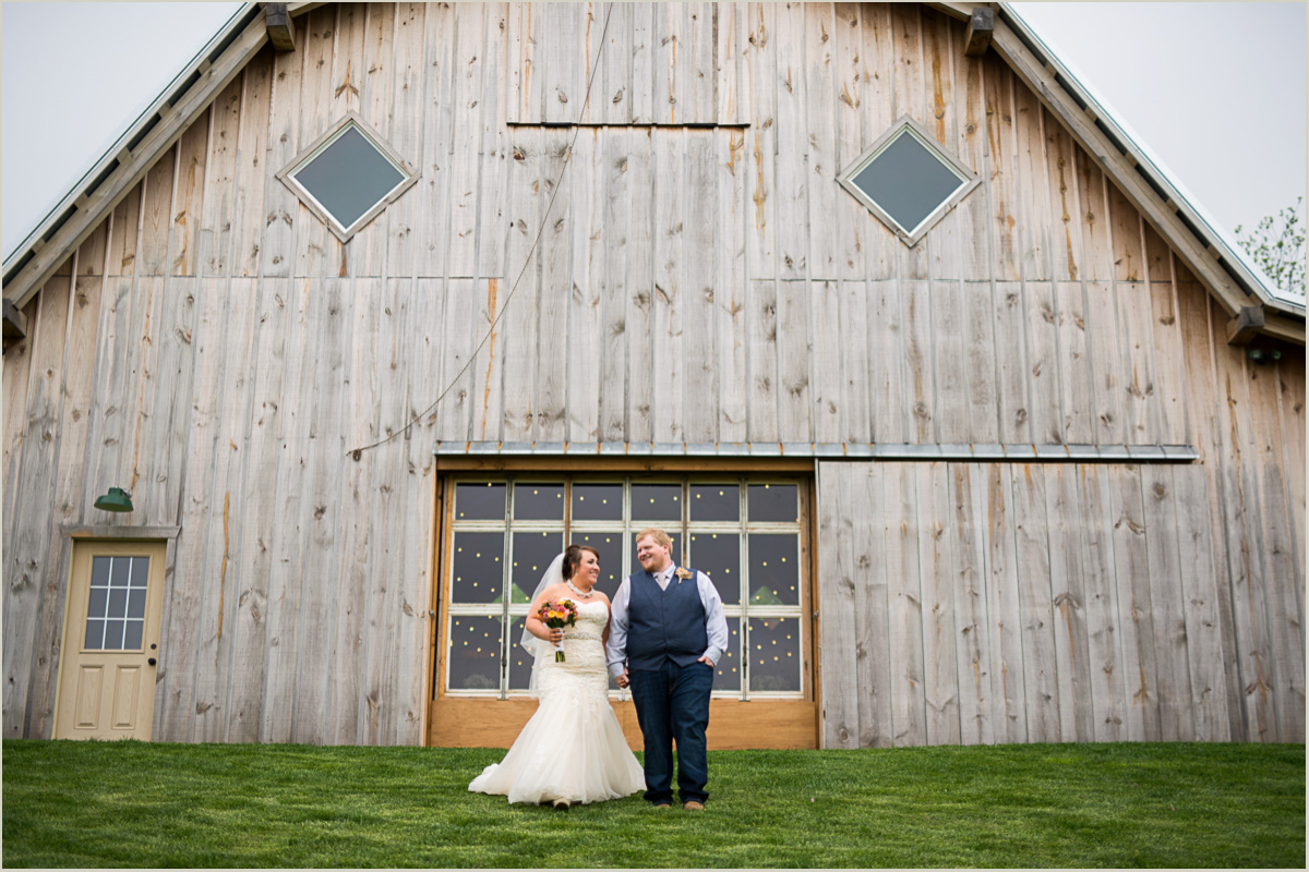 Bride and Groom Walking in Front of Barn Candid Wedding Photographers
