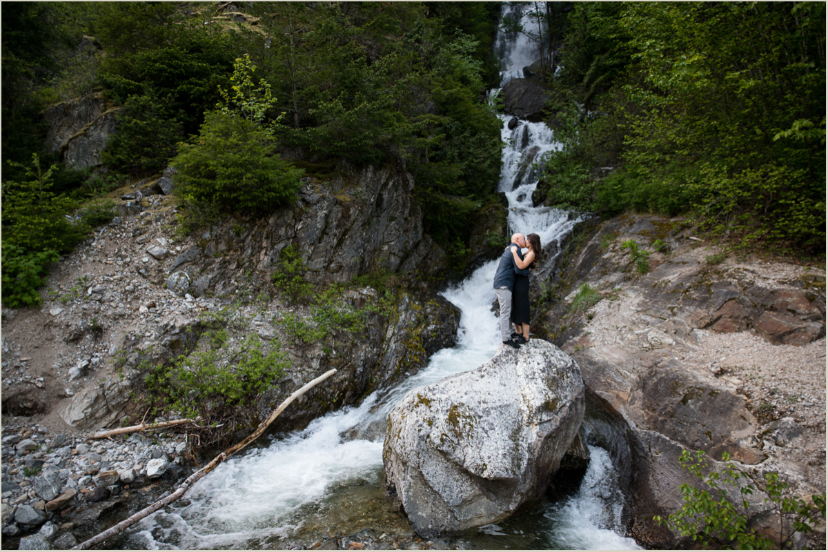 Couple Standing on a Boulder in front of a waterfall