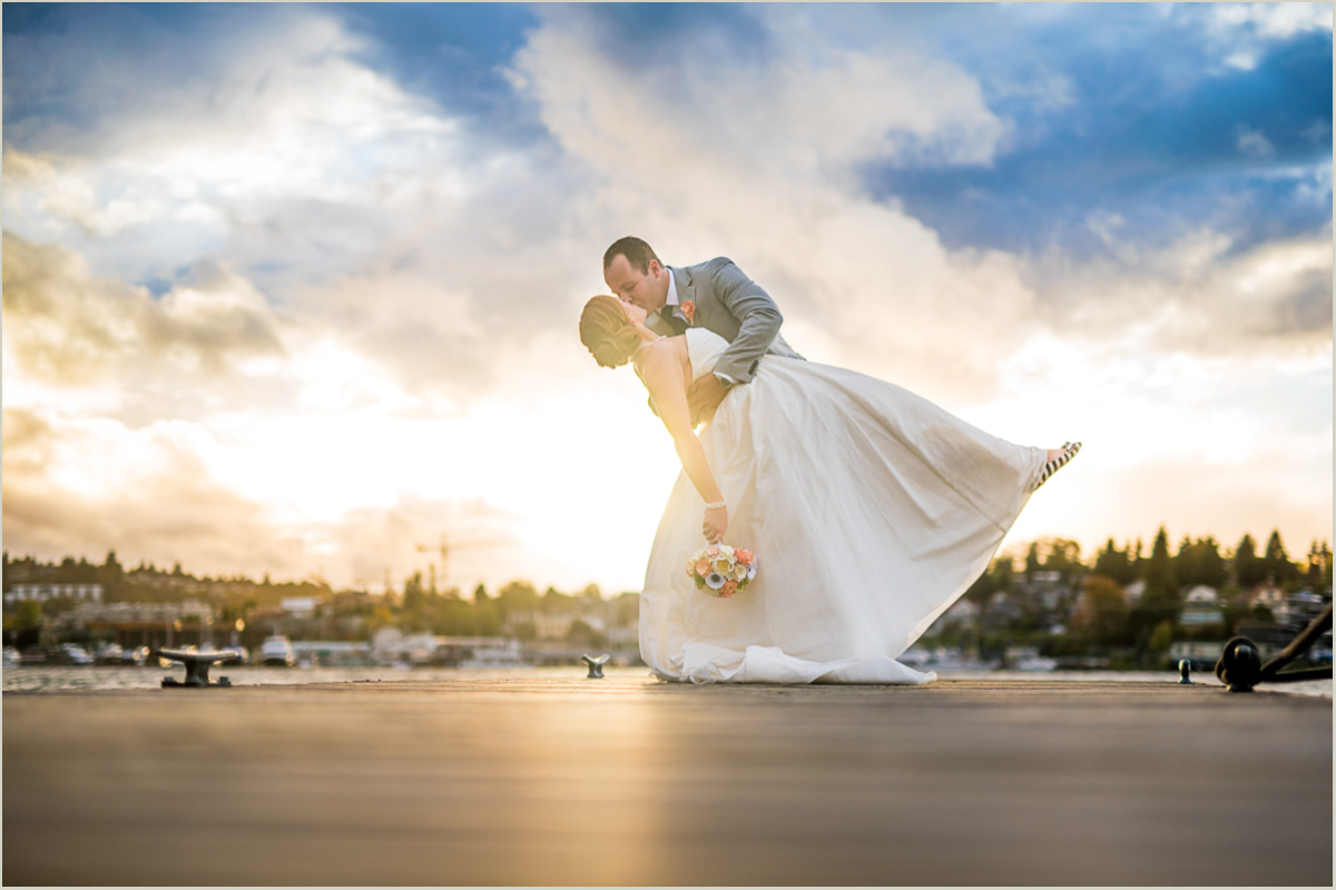 Groom dipping his bride at sunset on a dock on Lake Union