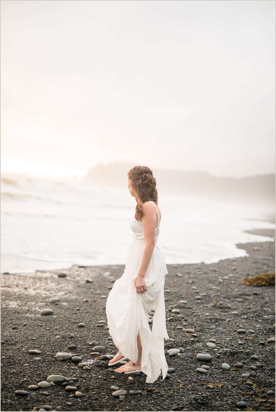 bride-standing-on-the-beach-at-sunset