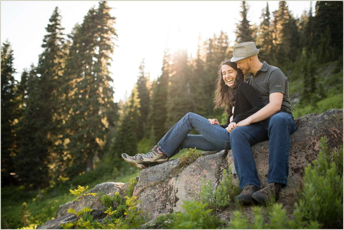 couple-sitting-on-a-rock-in-the-mountains-laughing