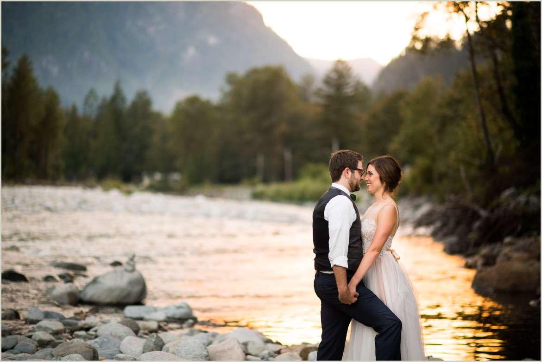 bride and groom kiss on river bank