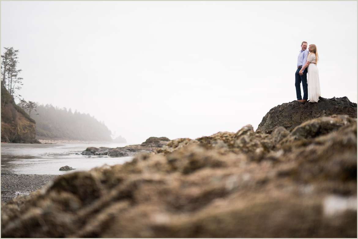 dramatic image of couple standing on rocky beach
