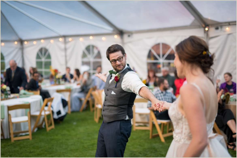 groom twirls bride around on dance floor