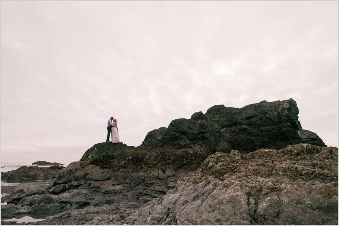 silhouette of couple standing on sea stack on coast