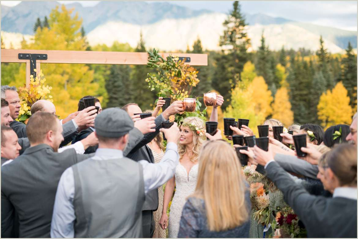 bride and groom cheers with guests during mountain ceremony