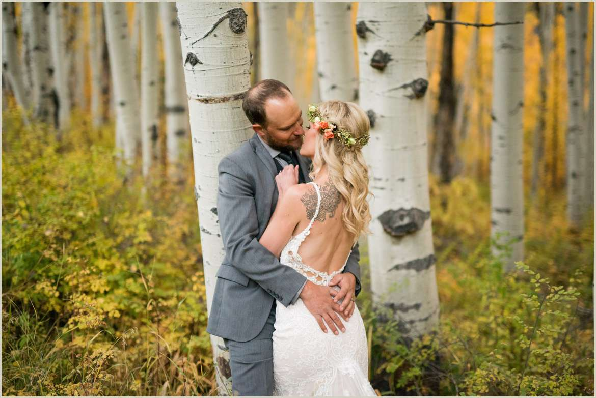 bride and groom kissing in aspens