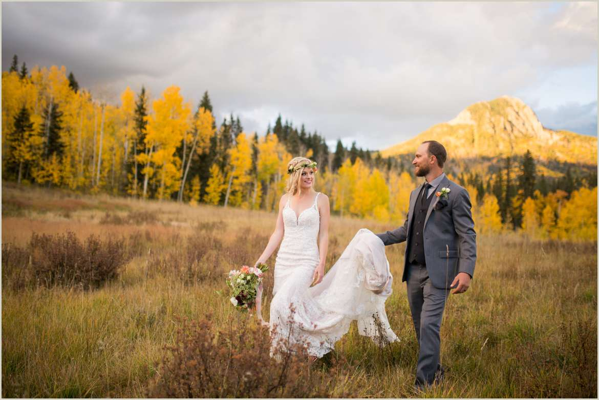 bride and groom walking in field with aspens