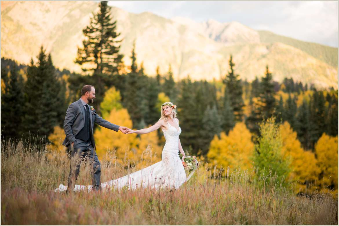 bride leading groom across mountain backdrop