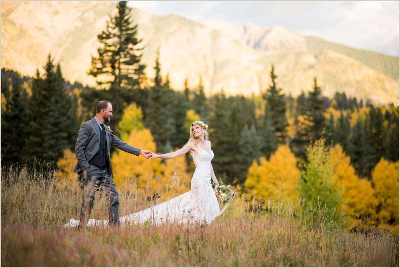 bride leading groom across mountain backdrop
