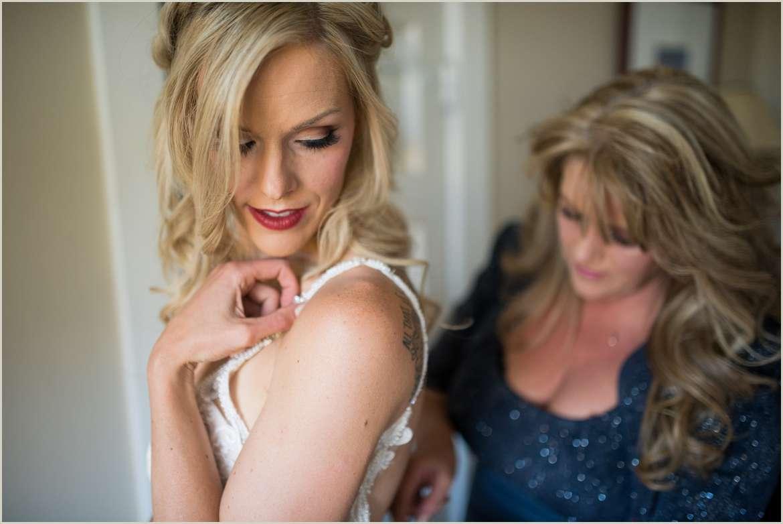 brides mom putting brides dress on