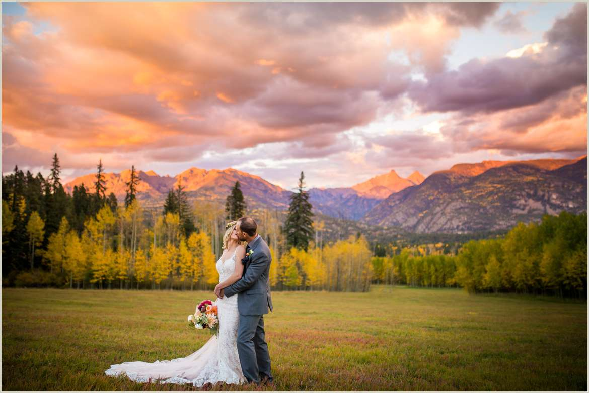 colorful fall sunset lights up colorado mountains with bride and groom kissing