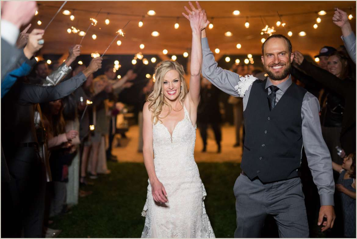 couple cheers as they exit wedding reception