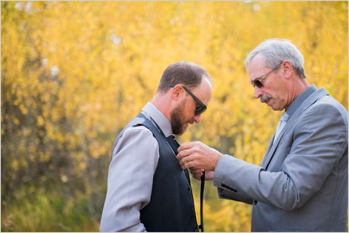 father of groom helping tie a tie