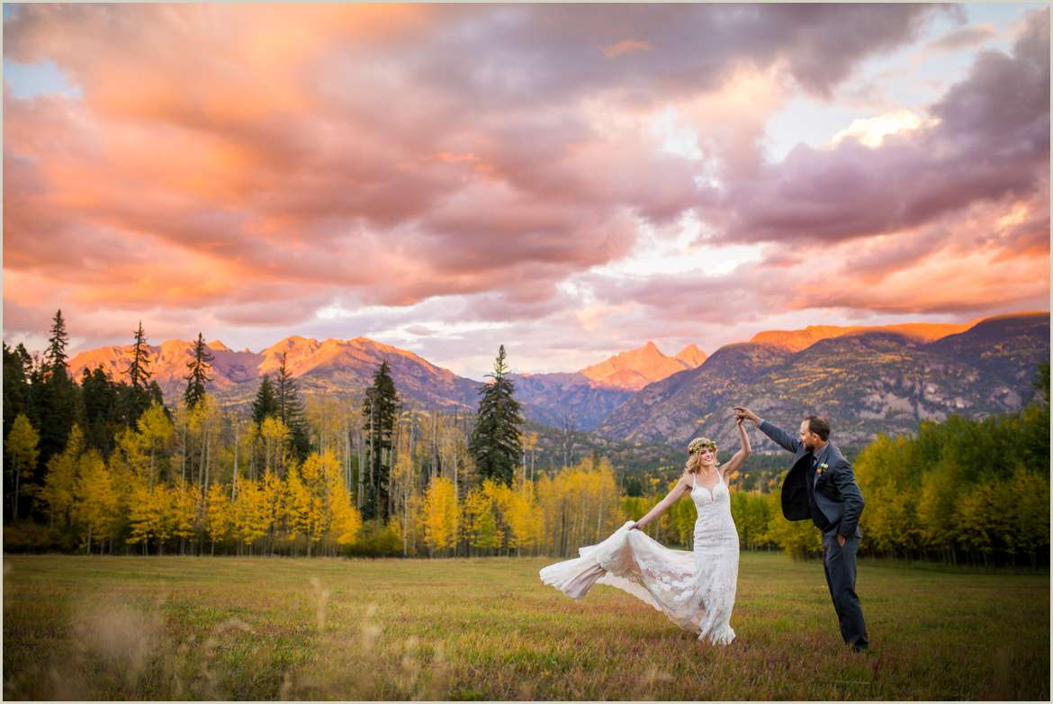 groom twirls bride romantically in the colorado mountains