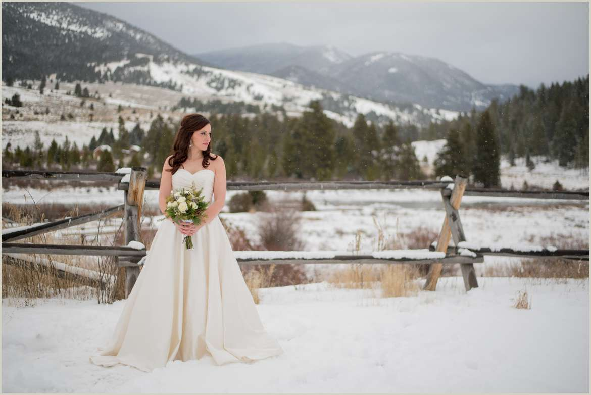 bride posing in front of fence on ranch in montana winter
