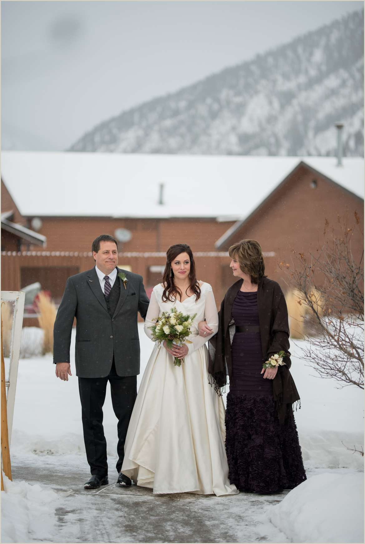 bride walking down aisle with both parents
