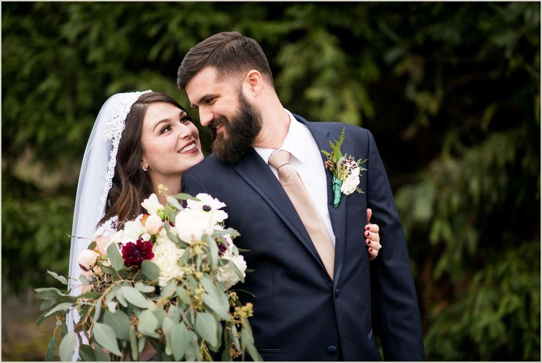 dapper groom looks at his stunning bride