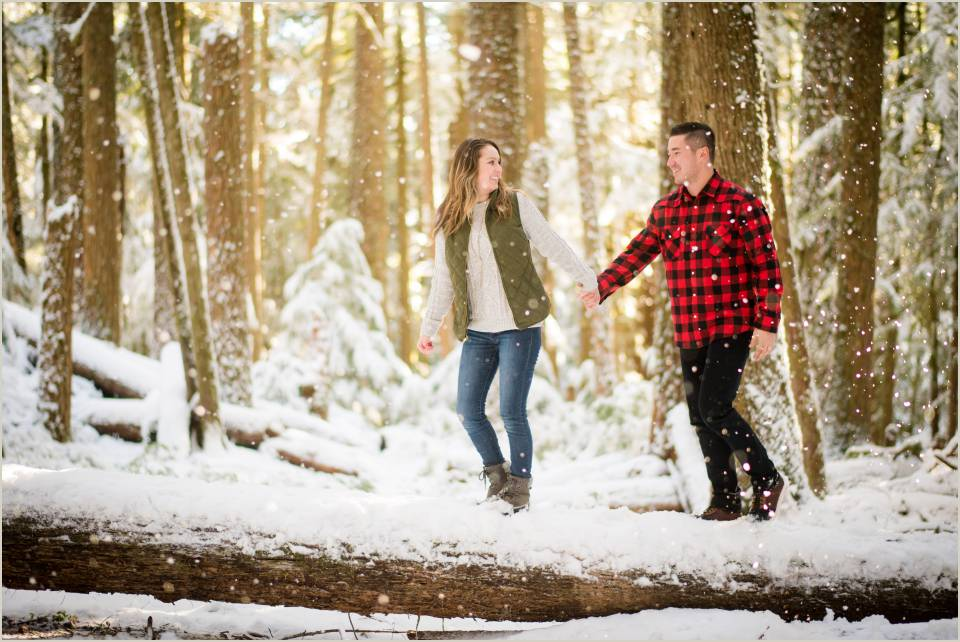 engaged couple hiking log winter ranier
