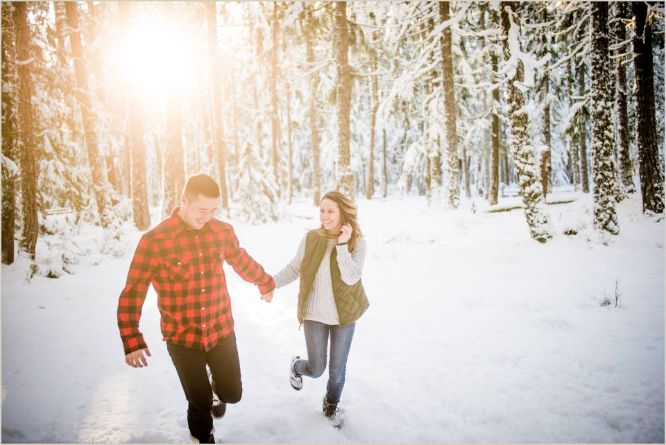 fun adventurous couple running through snowy forest