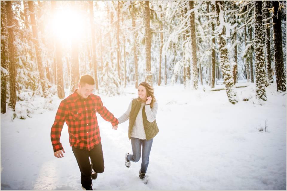 fun adventurous couple running through snowy forest