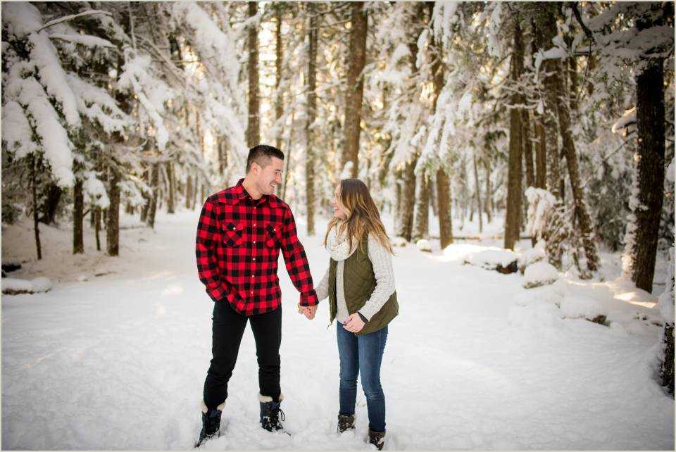 fun loving couple snowy forest engagemet photos