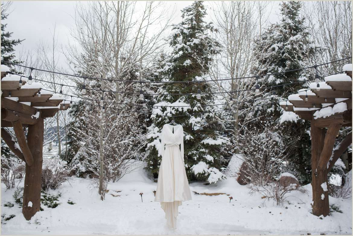 wedding dress hanging in snow covered courtyard