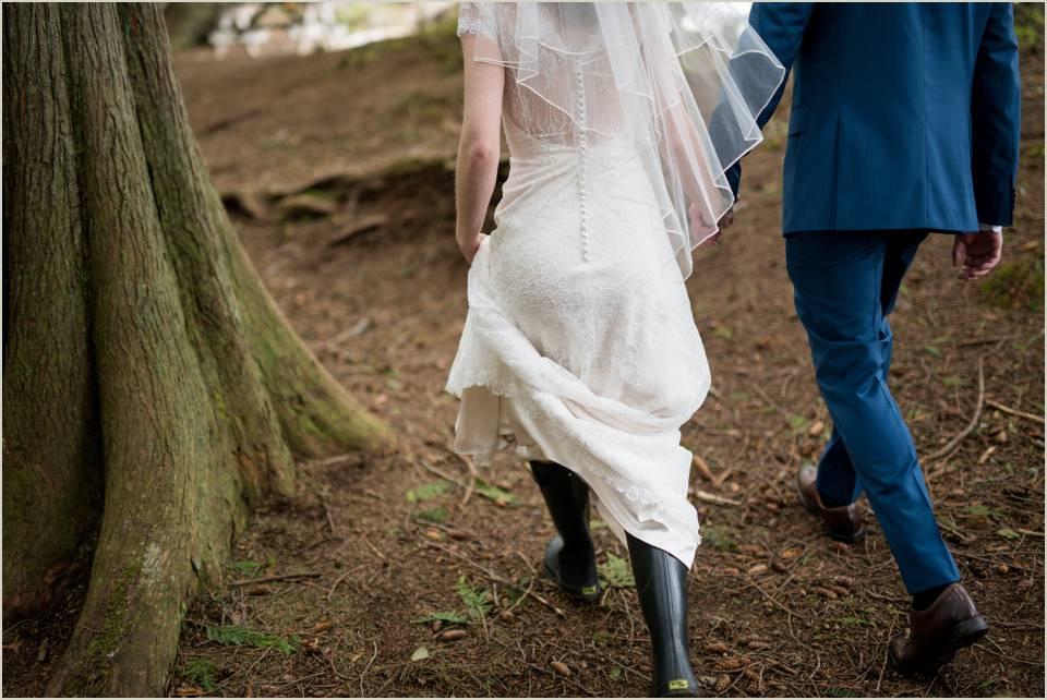 couple hiking through woods in wedding attire