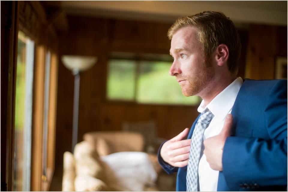 groom putting suit jacket on