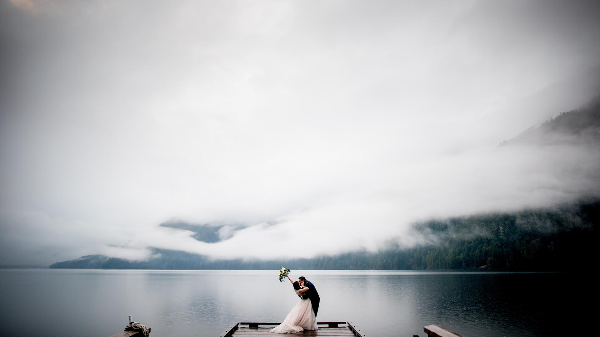 passionate kiss at sunset on lake crescent elopement featured