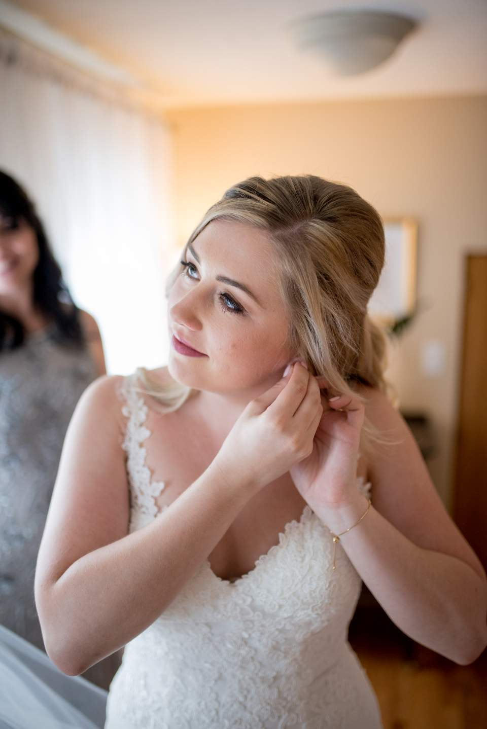 beautiful bride putting her earrings on