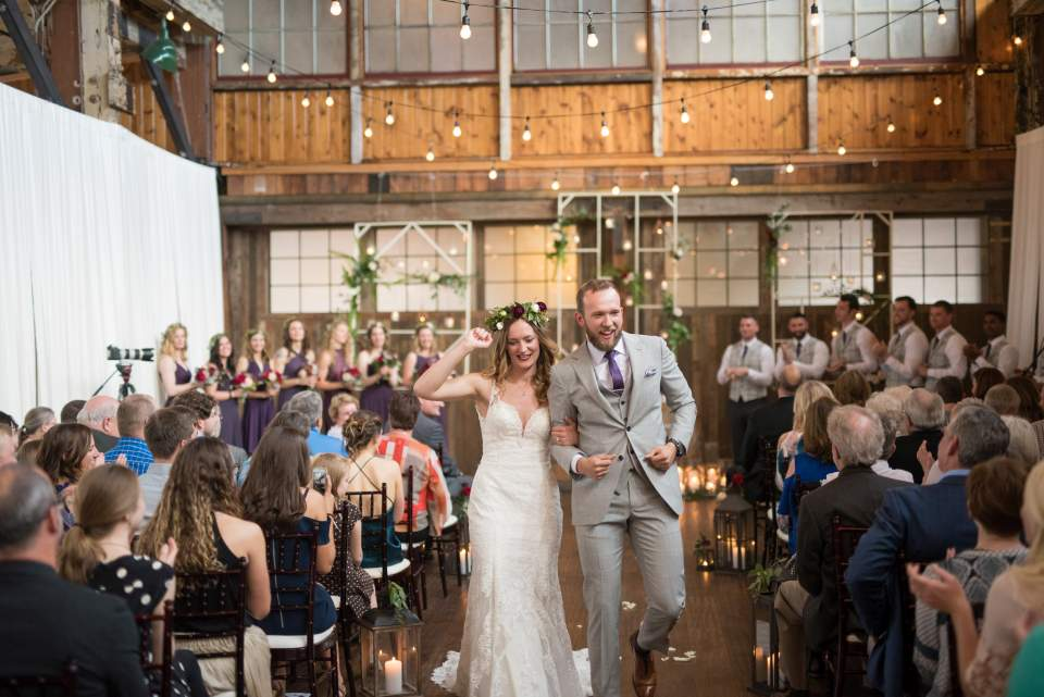 bride and groom dancing down aisle