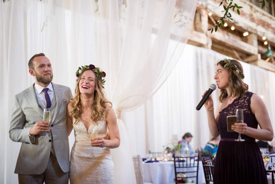 bride and groom reacting to maid of honor toast