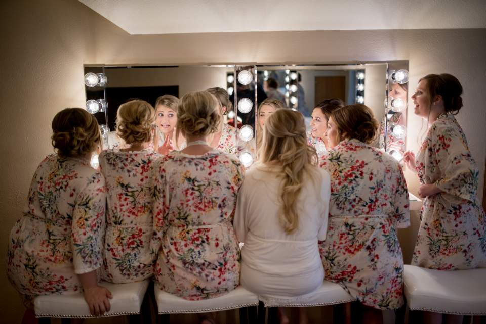 bride with all her maids getting ready for wedding in mirror