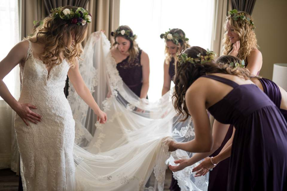 bridesmaids helping bride with train