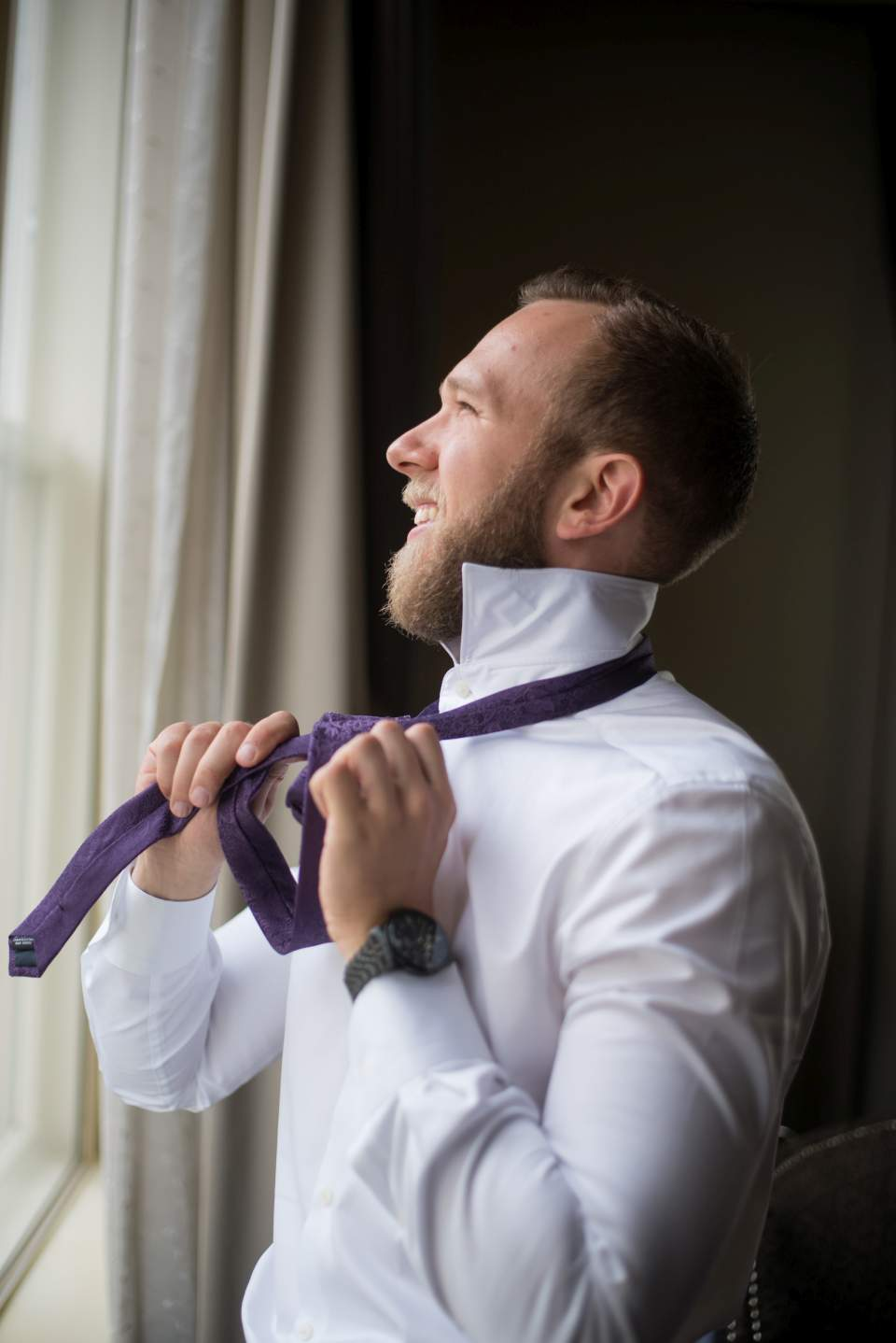 candid wedding photos of groom putting tie on