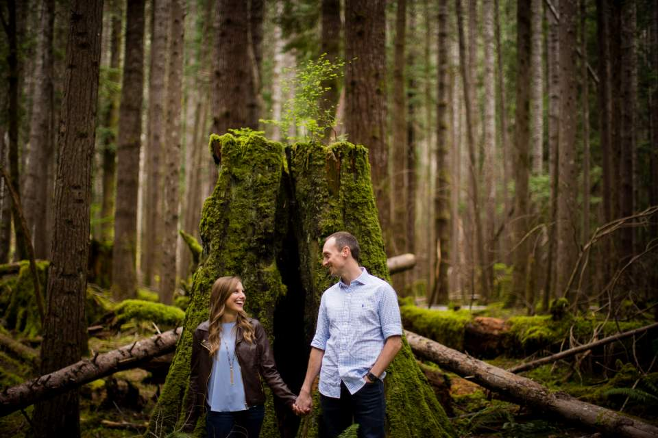 couple holding hands in mossy forest