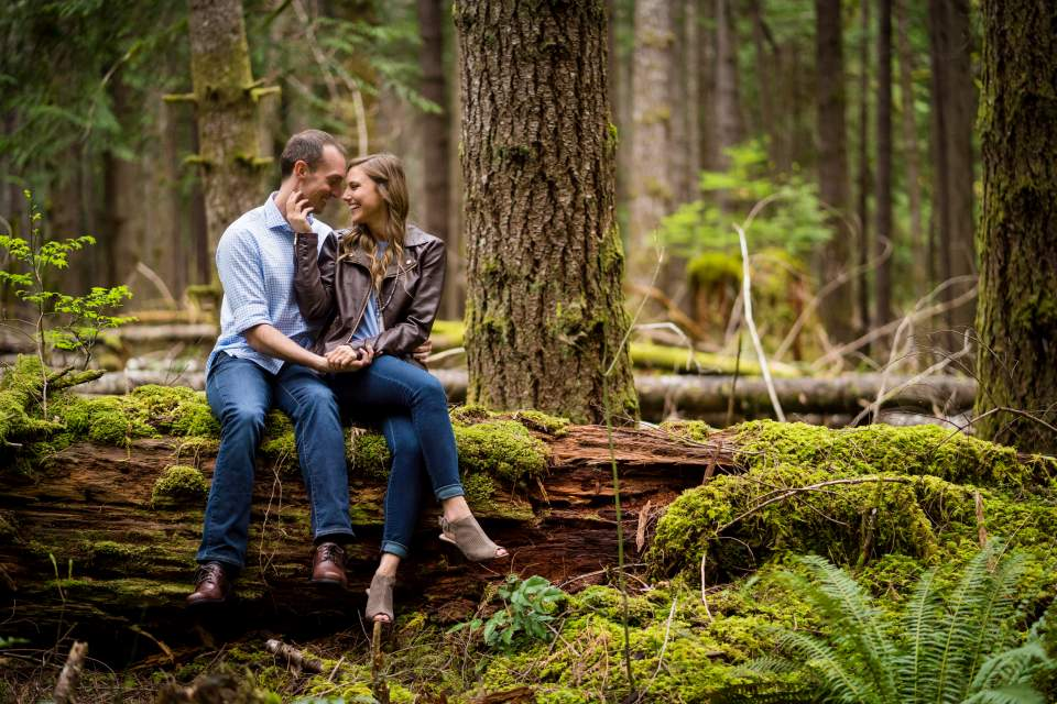 couple sitting on a log in a mossy forest