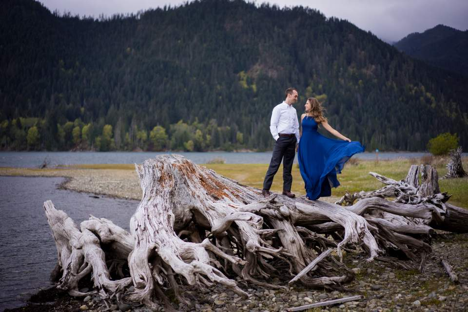 couple standing on tree roots at pnw lake