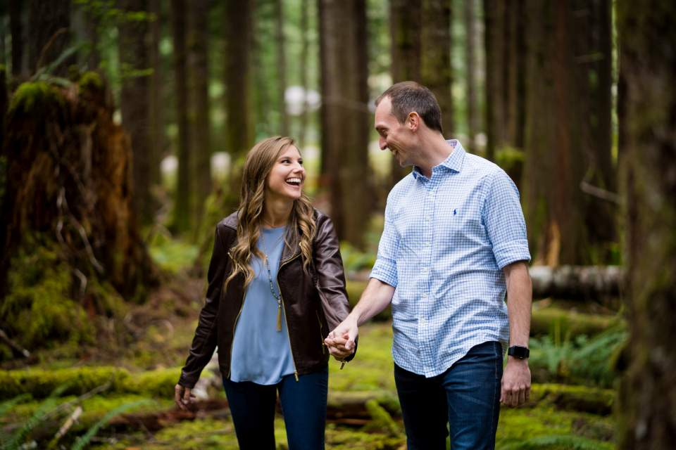 couple walking through mossy forest