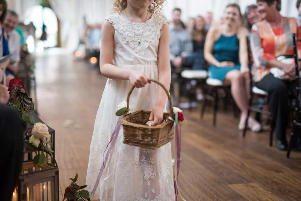 detail of flower girl walking down aisle