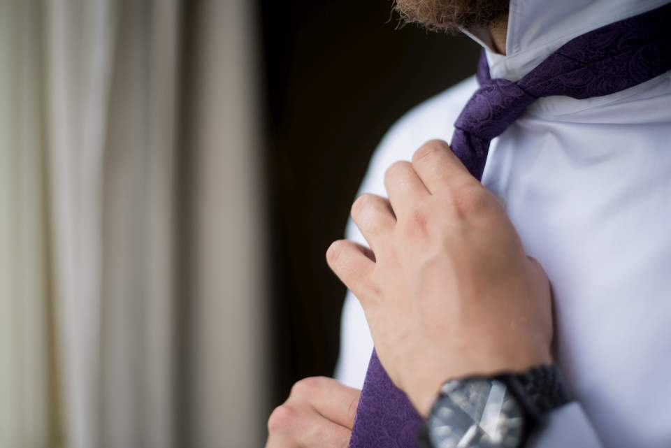detail of groom tying tie