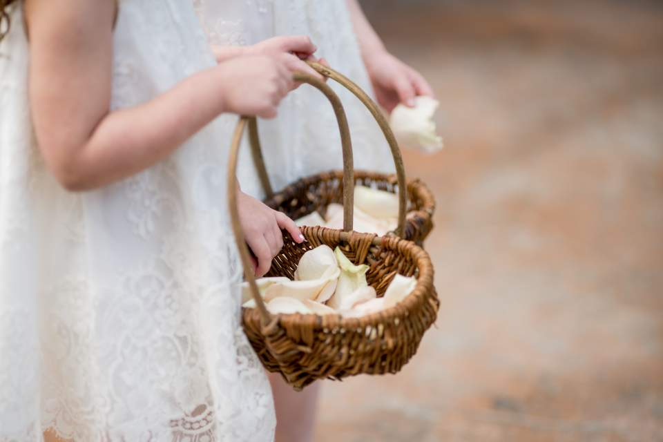 detail photo of flower girls sprinkling petals on aisle