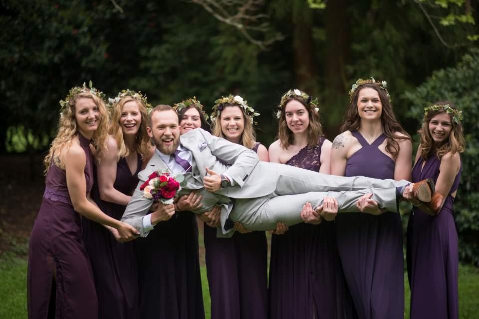 fun bridesmaids holding groom photo