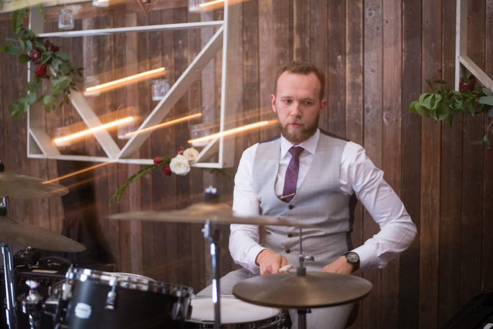 groom playing drums with wedding band