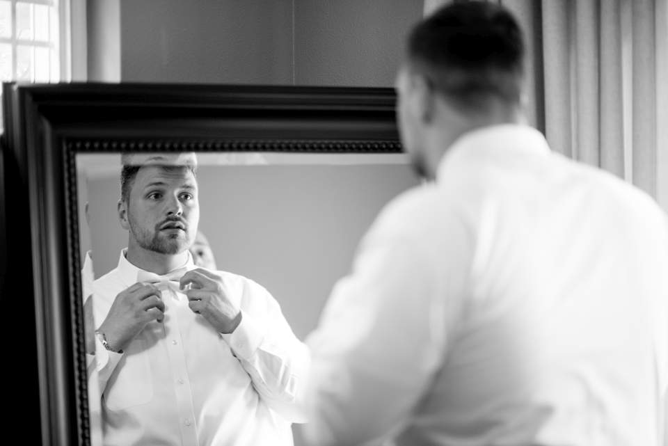 groom trying his bow tie
