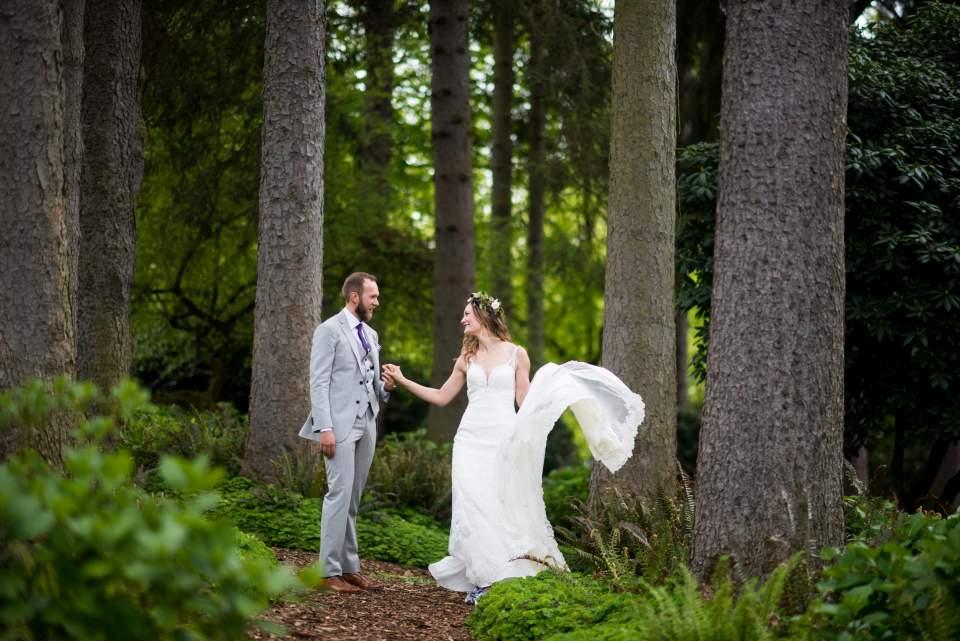groom twirling bride in the trees