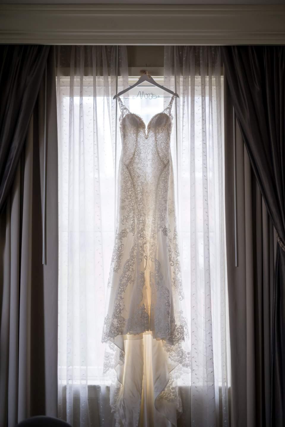 lace wedding dress hanging in window